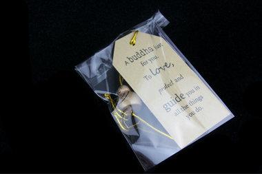Gelukszakje kraft label tekst met gelukspoppetje boeddha goud